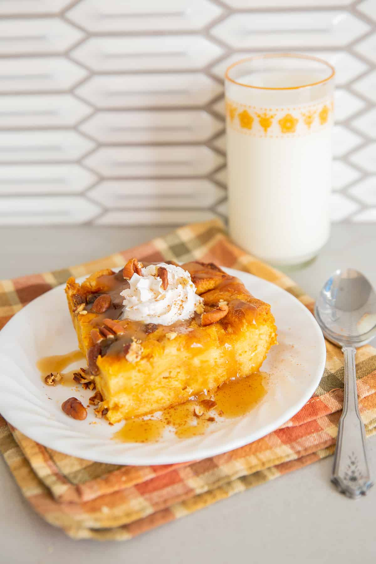 Pumpkin Bread Pudding on a white plate, a glass of milk on background