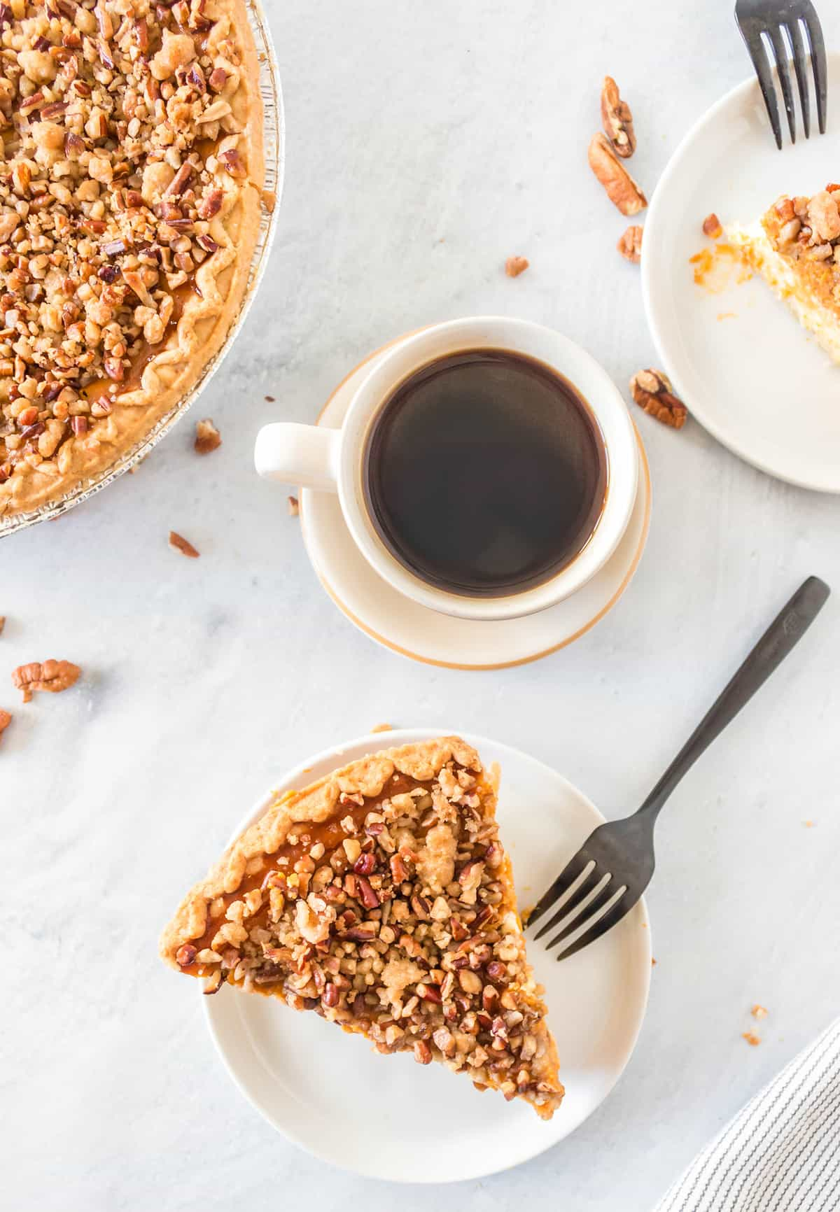 top down shot of Pumpkin Cheesecake Pie slice in a white plate and a cup of coffee beside it