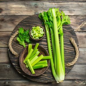 Celery on a wood cutting board.