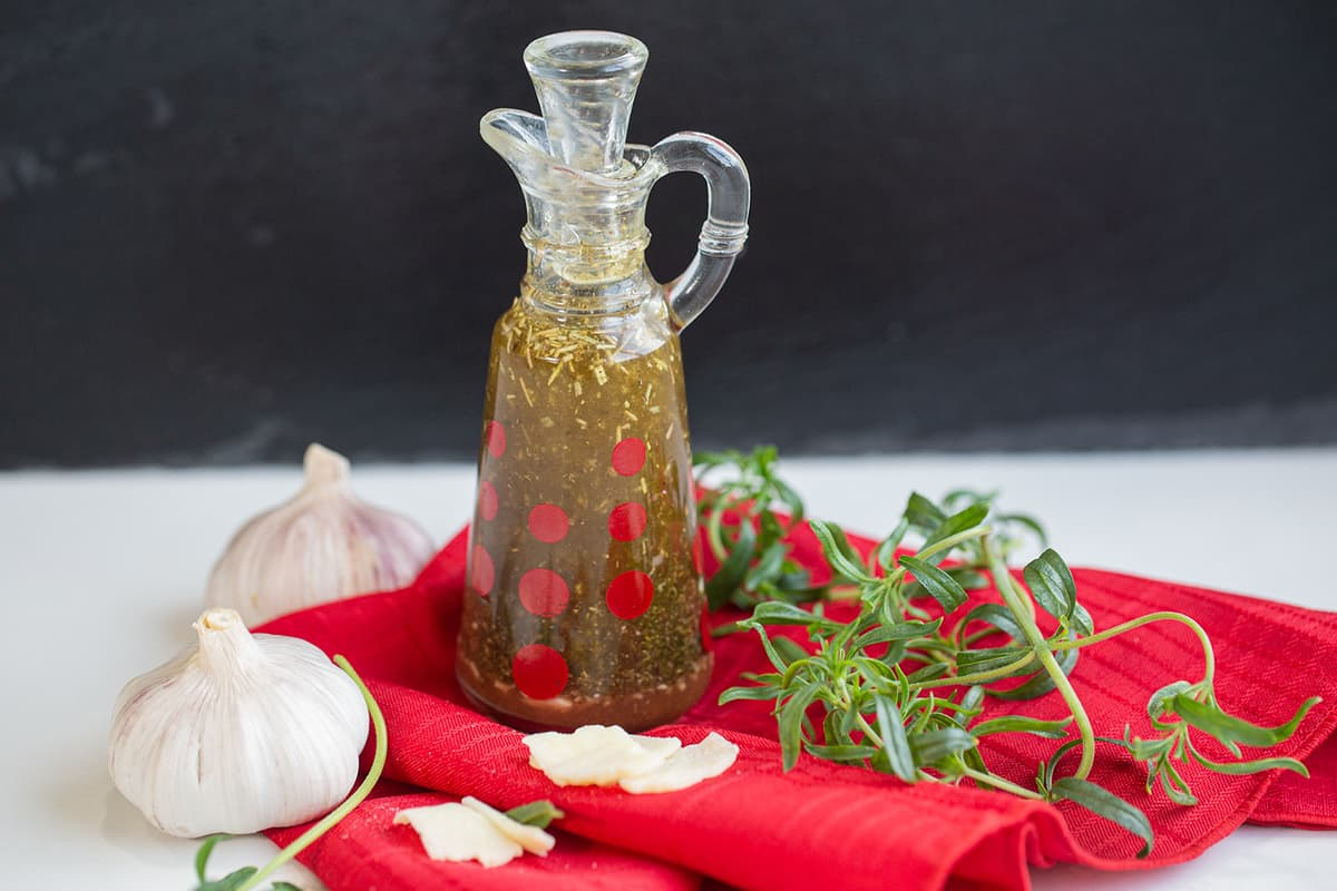 red cloth underneath the oil and vinegar based Italian Dressing in a transparent container