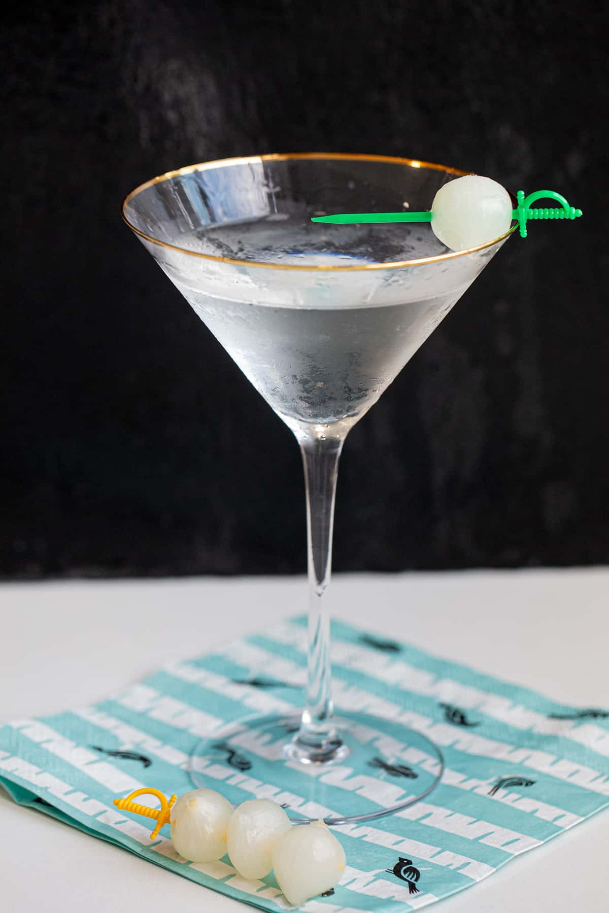 Gibson Cocktail on a black background garnished with pickled onion