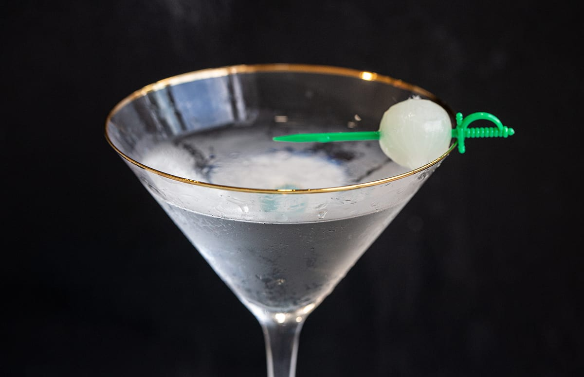 Gibson Cocktail on a black background garnished with a pickled onion