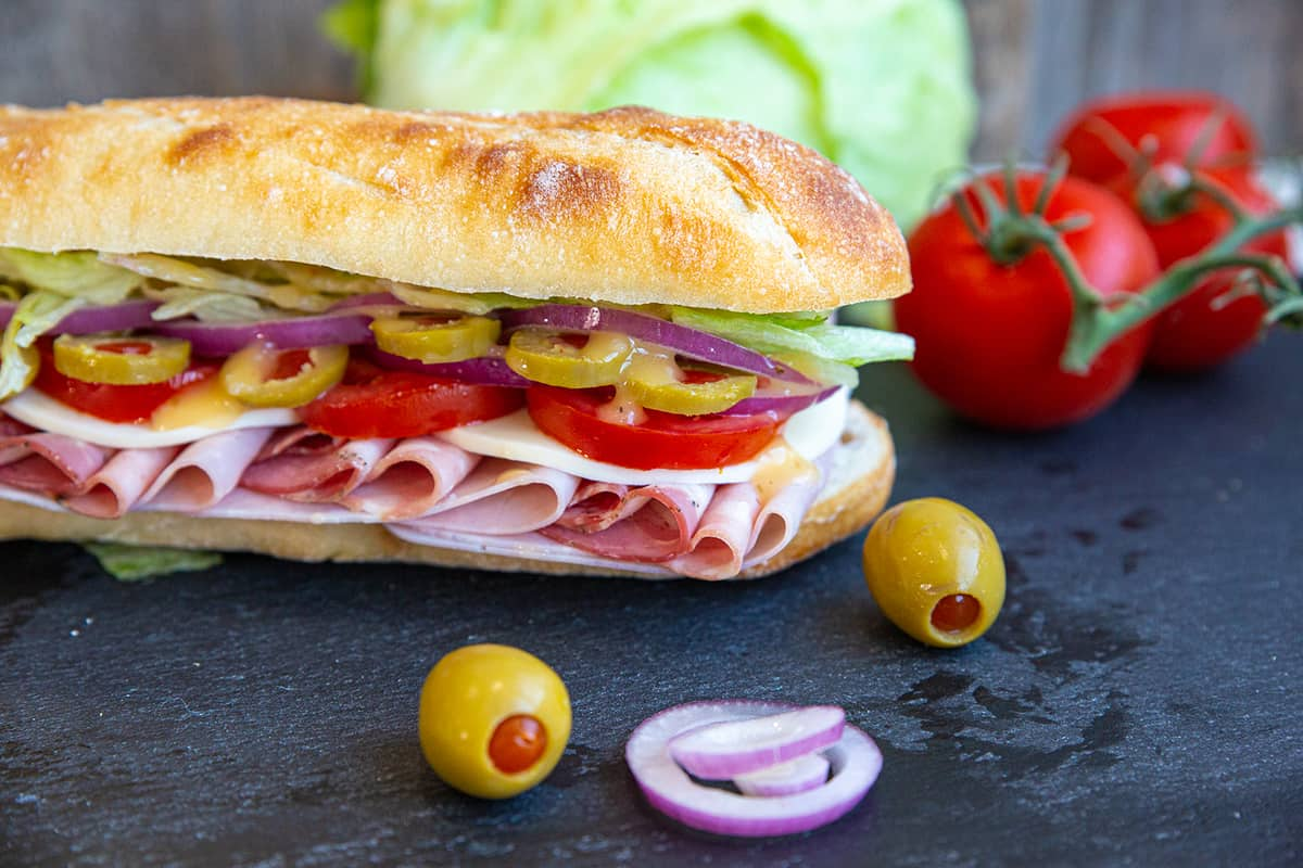 Close up of Italian Sub on a black slate board with olives, onion, tomatoes and lettuce surrounding it.