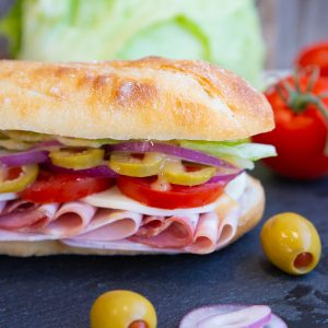 Close up of Italian Sub on a black slate board with olives, onion, tomatos and lettuce surrounding it.