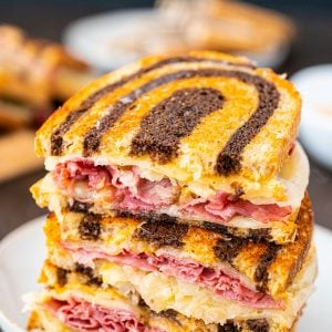 Reuben Sandwich on a white plate with russian dressing in the background