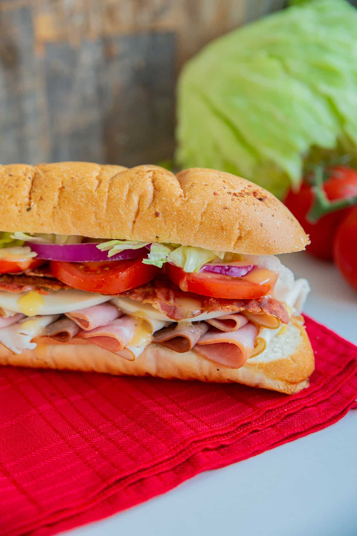 close up Submarine Sandwich on a red napkin with tomatoes and lettuce.