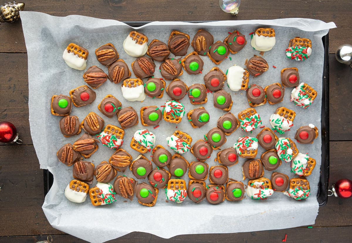 Top down shot of rolo pretzel cookies, decorated in different ways, on a parchment lined baking sheet.