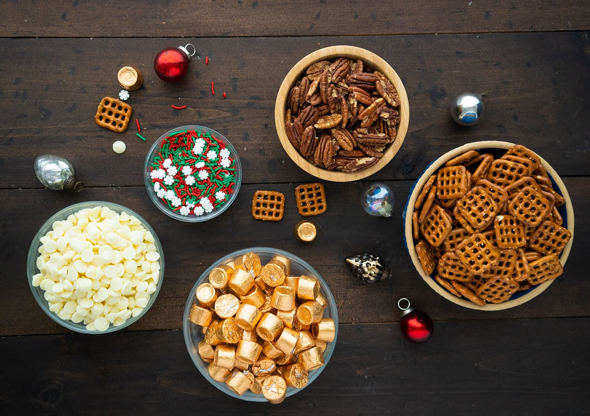 Pecans, pretzels, rolo candies, melting candy and sprinkles, all in different bowls.