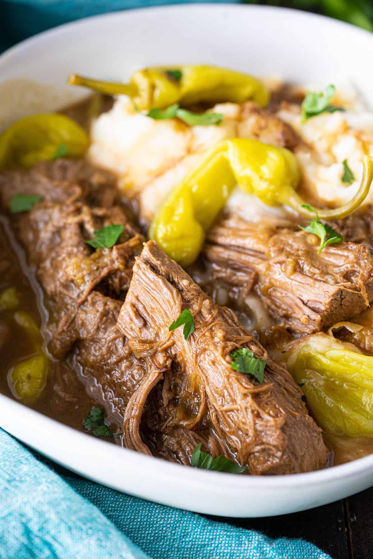A close up shot of a Mississippi pot roast, shredded meat on the top with peppers.