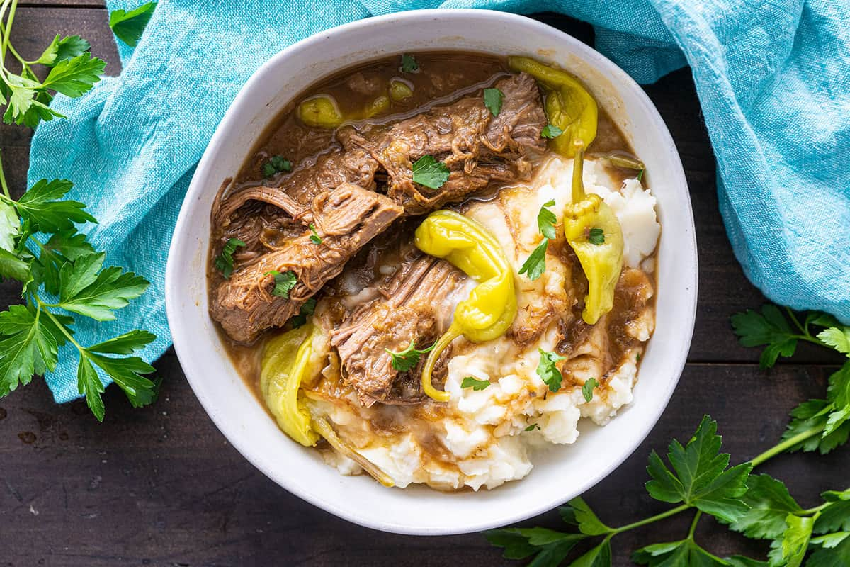 Top down photo of a finished Mississippi pot roast, topped with pepperoncini peppers
