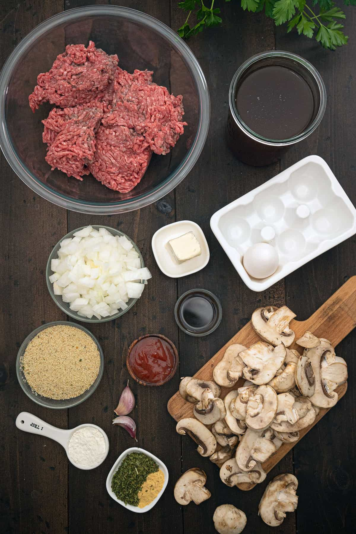 A top down shot of the Ingredients of salisbury steak, all layed out in bowls.
