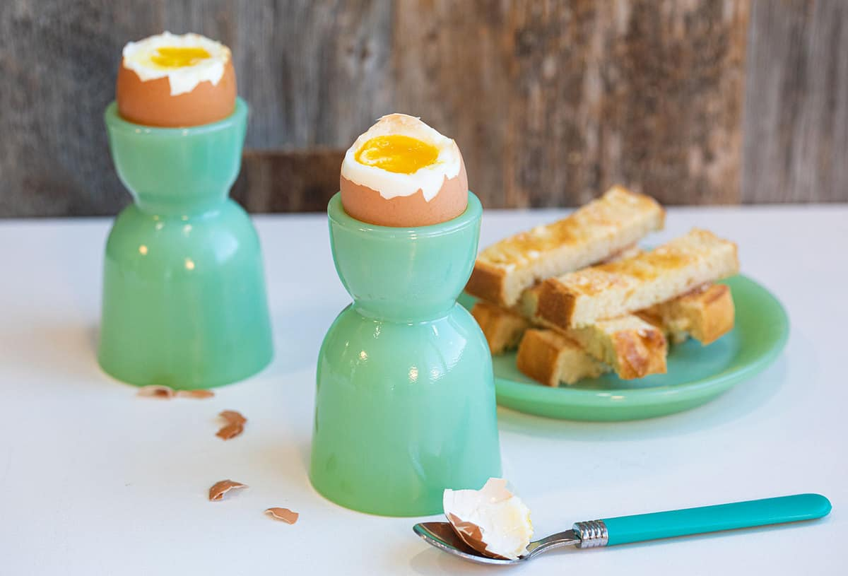 Soft boiled eggs with their tops removed, showing the inner yolk, next to some toast soldiers on jadeite kitchenware.