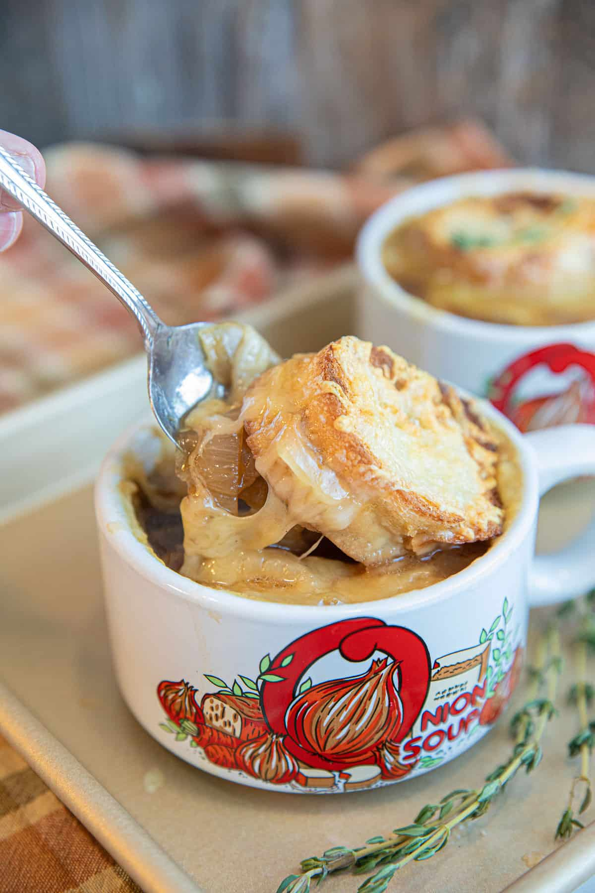French Onion Soup in a white handled bowl with toasted cheese on top