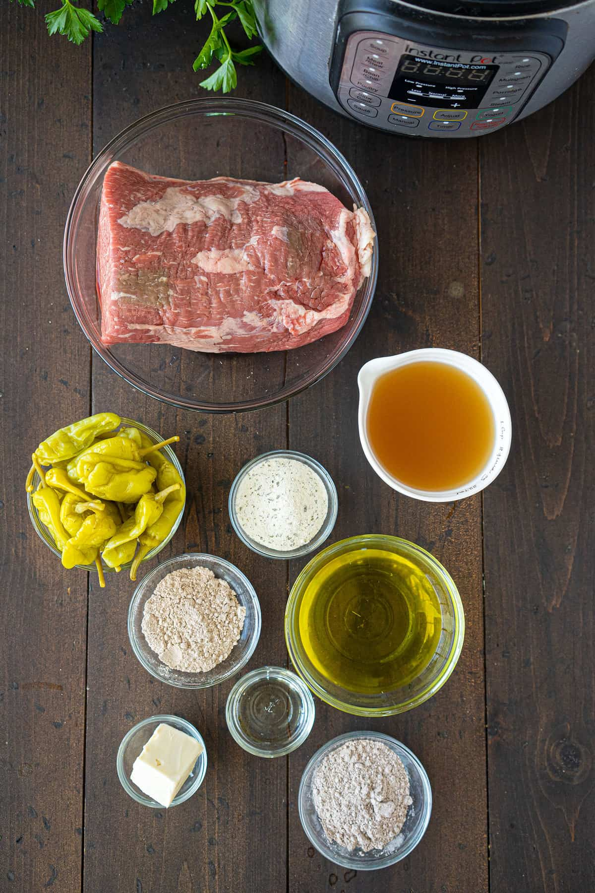 The ingredients for a Mississippi pot roast, laid out in individual bowls next to an Instant Pot