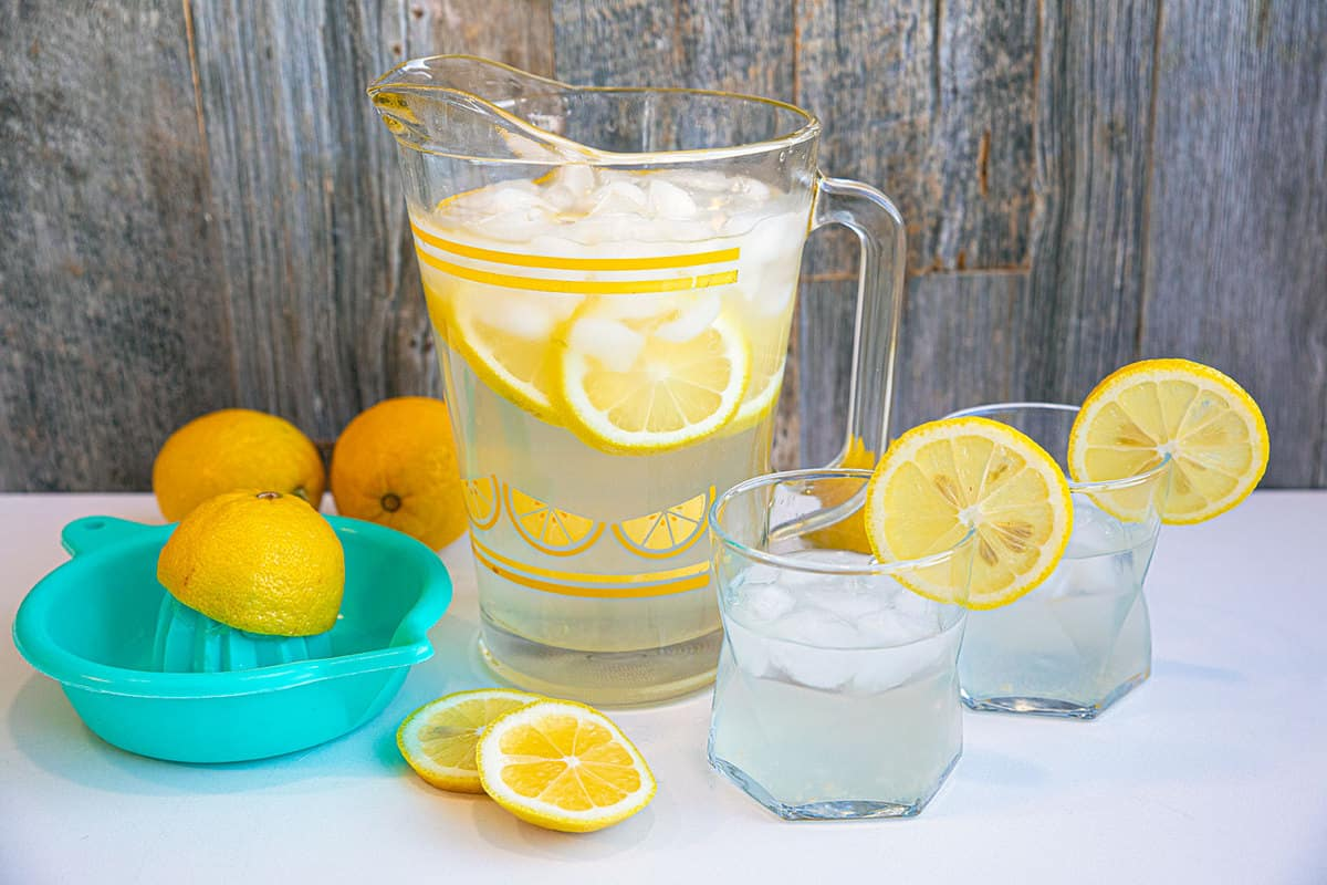Lemon Water on the counter in two glasses with a pitcher in the background