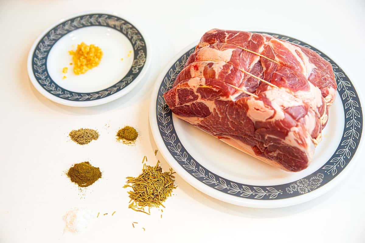 top down shot of a tied up, raw pork shoulder, with the seasoning ingredients on plates