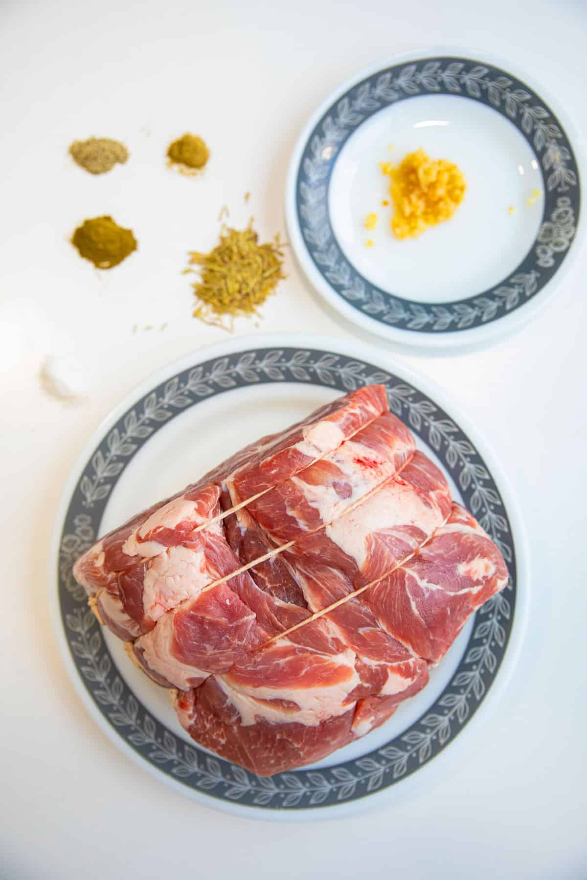 top down shot of a tied up, raw pork shoulder, with the seasoning ingredients nearby