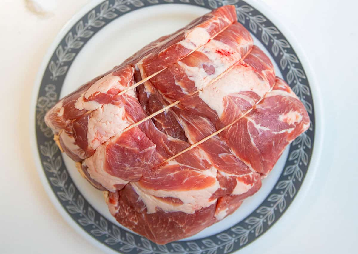raw pork shoulder roast on a plate