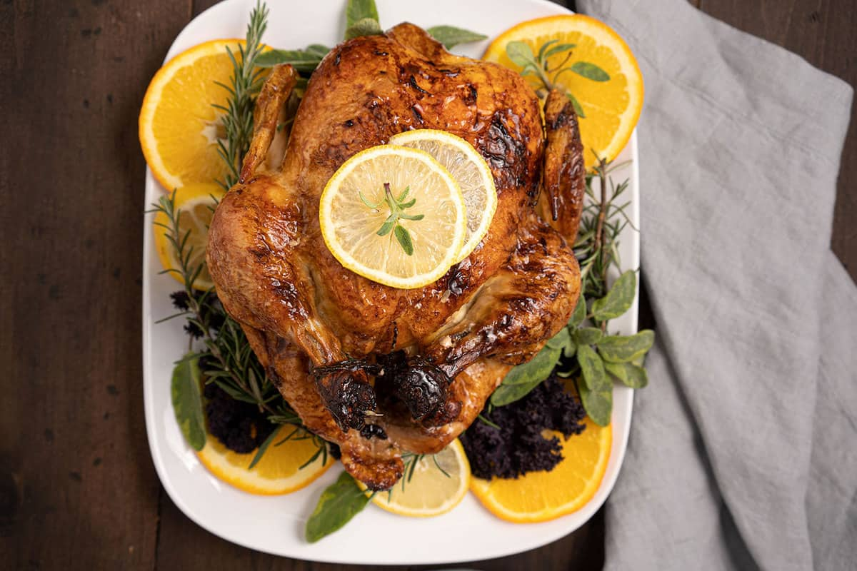 roasted chicken on a white plate with orange slices, lemon slices and rosemary.
