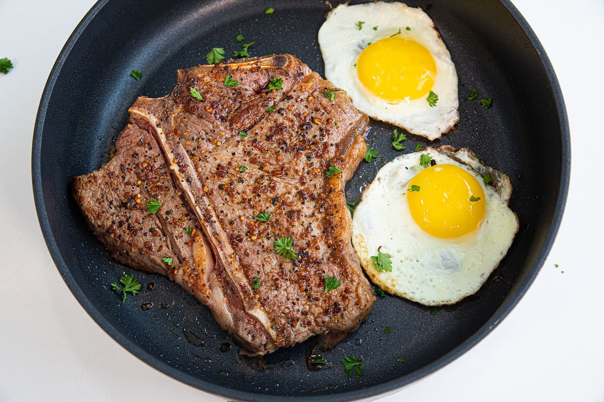 Top down shot of a t bone steak and two fried eggs on a cast iron pan