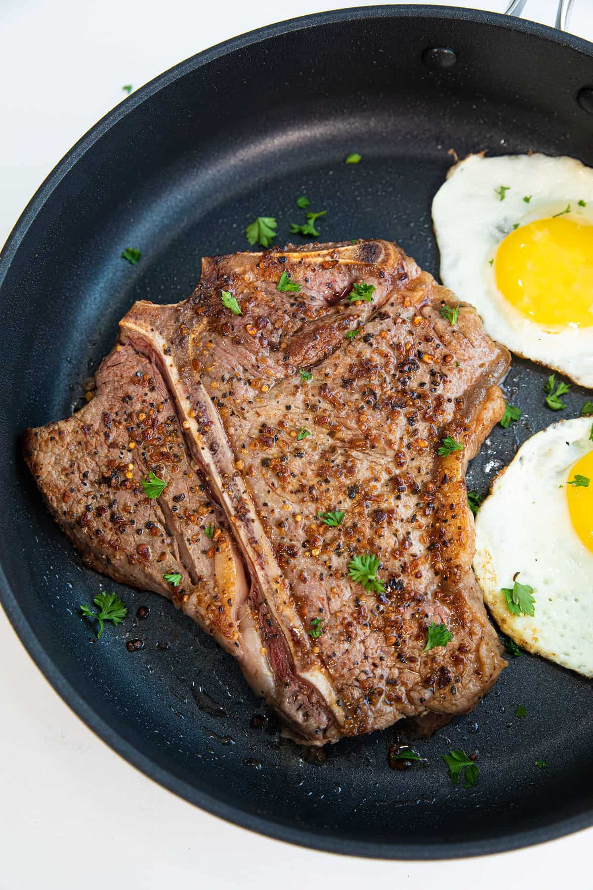 Close up of a T bone steak with two friend eggs next to it on a cast iron pan