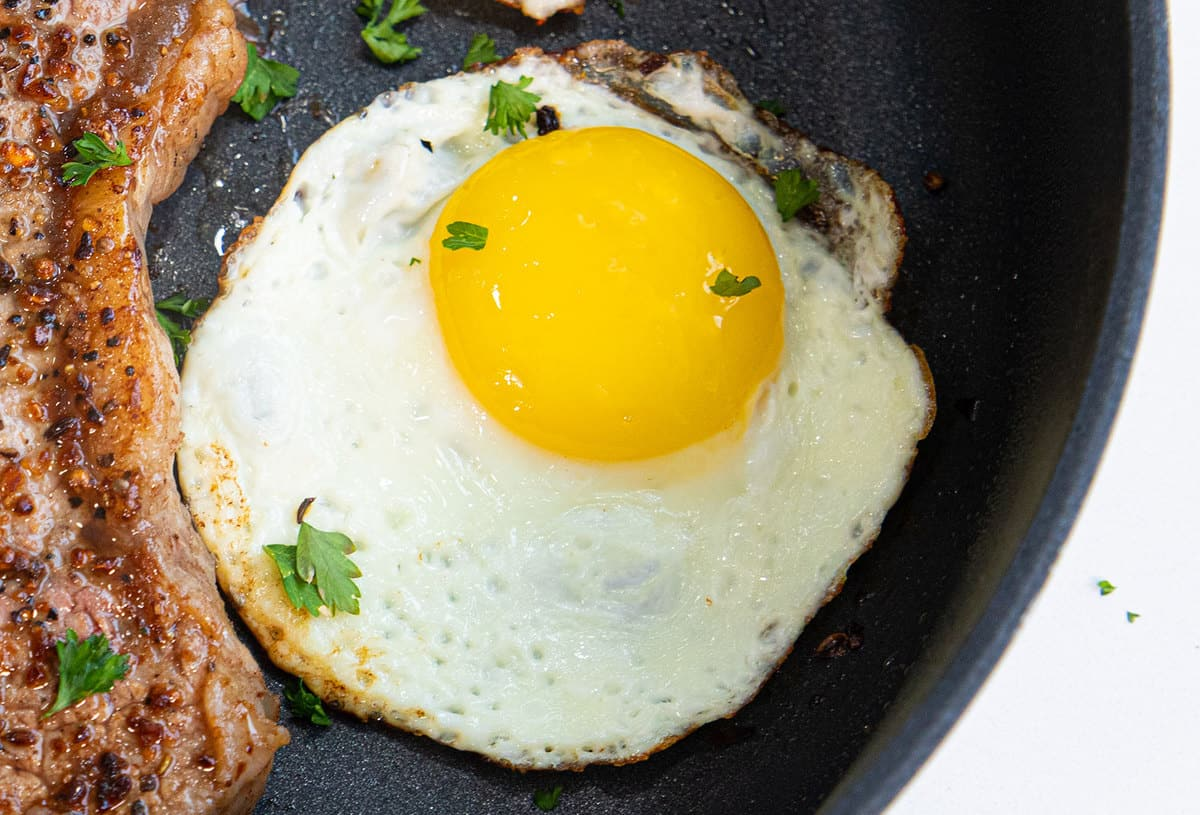 A close-up of a sunny side up fried egg, with flecked bits of parsley dotting the surface.