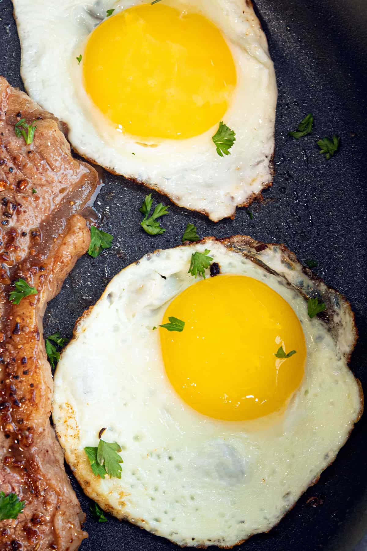 A close-up of two sunny side up fried eggs, next to the edge of a steak on a black plate, dotted with parsley