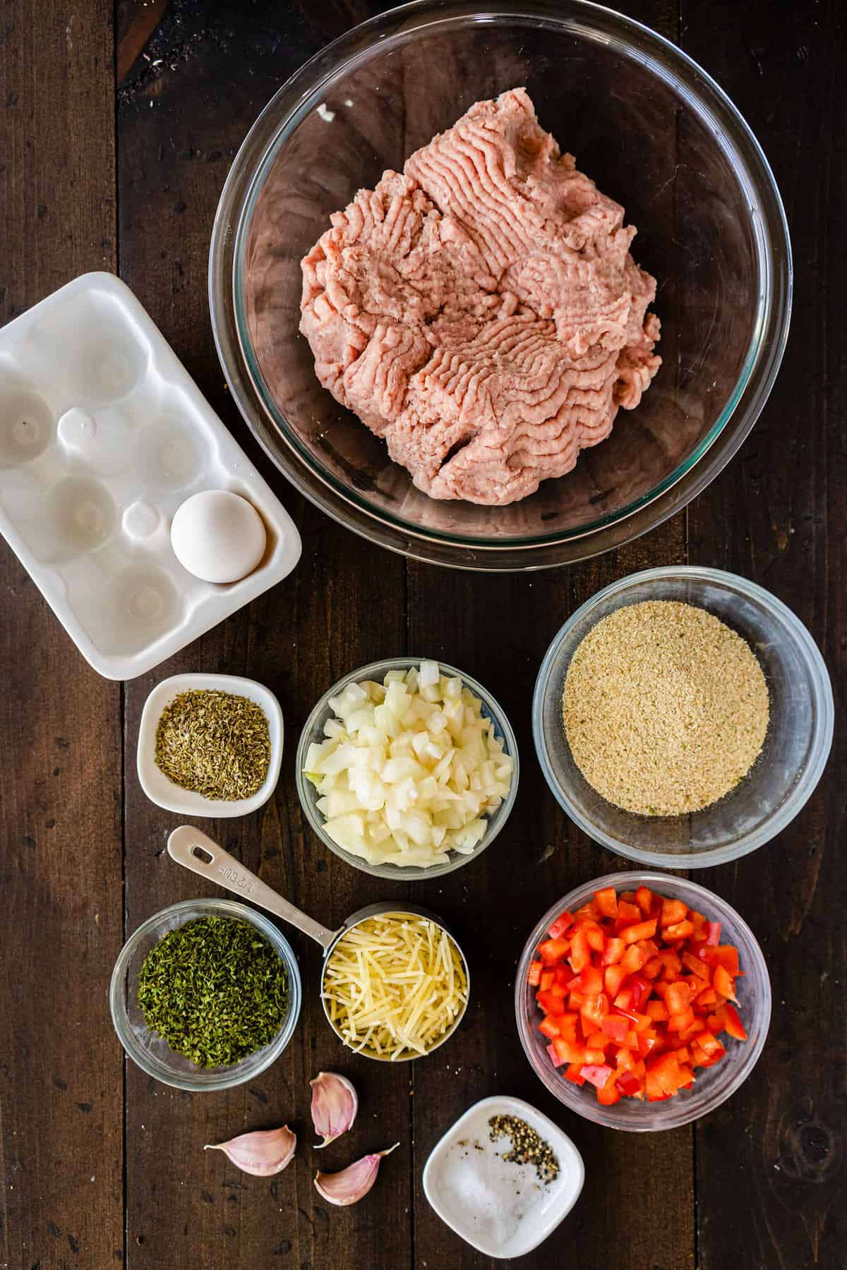 Component ingredients of a turkey meatloaf, all portioned out in bowls.