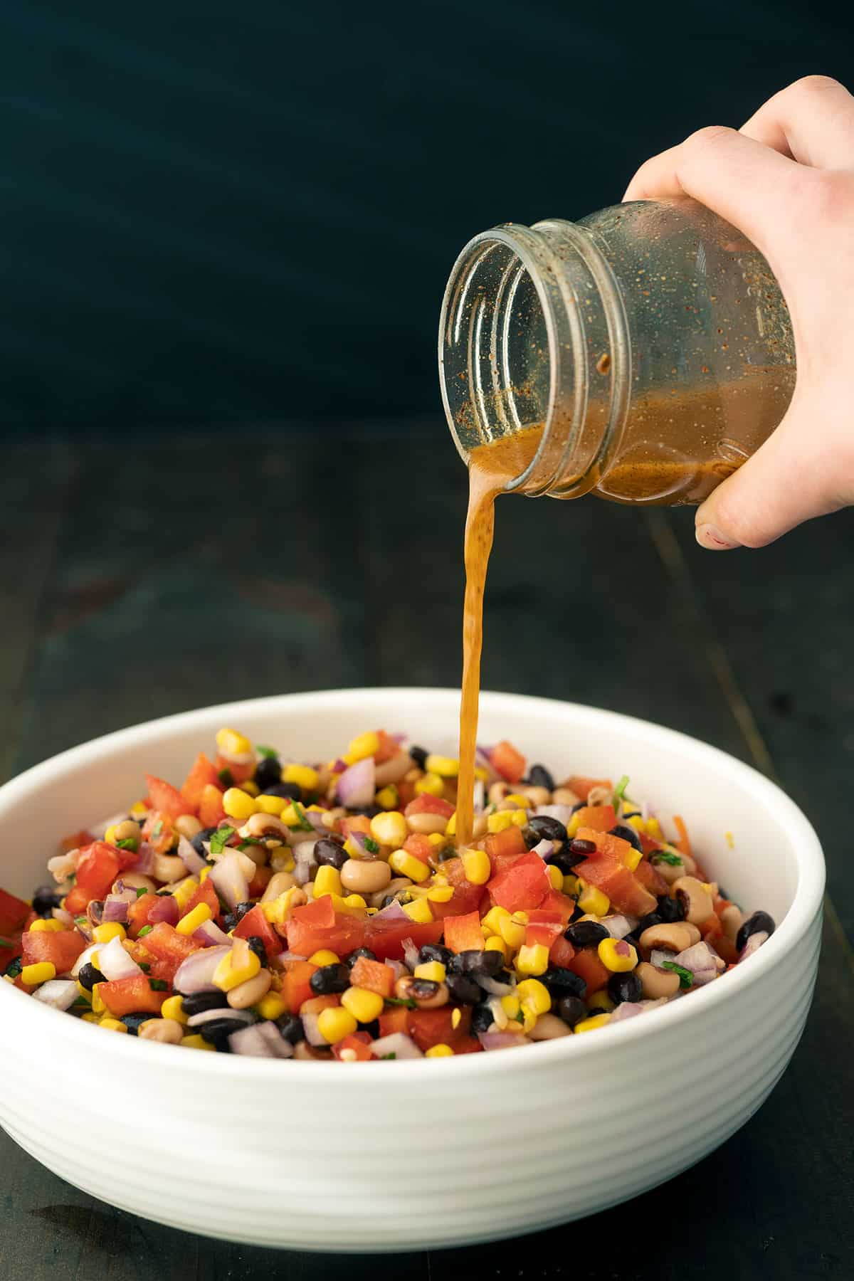 Spicy vinaigrette dressing being poured over a bowl of cowboy caviar.