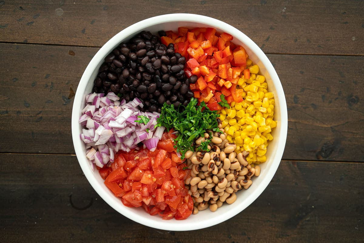 The main ingredients for Cowboy caviar, arranged in color order, in a large mixing bowl.