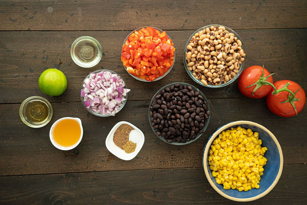 All the ingredients of cowboy caviar, seperated into glass bowls on a wooden table.