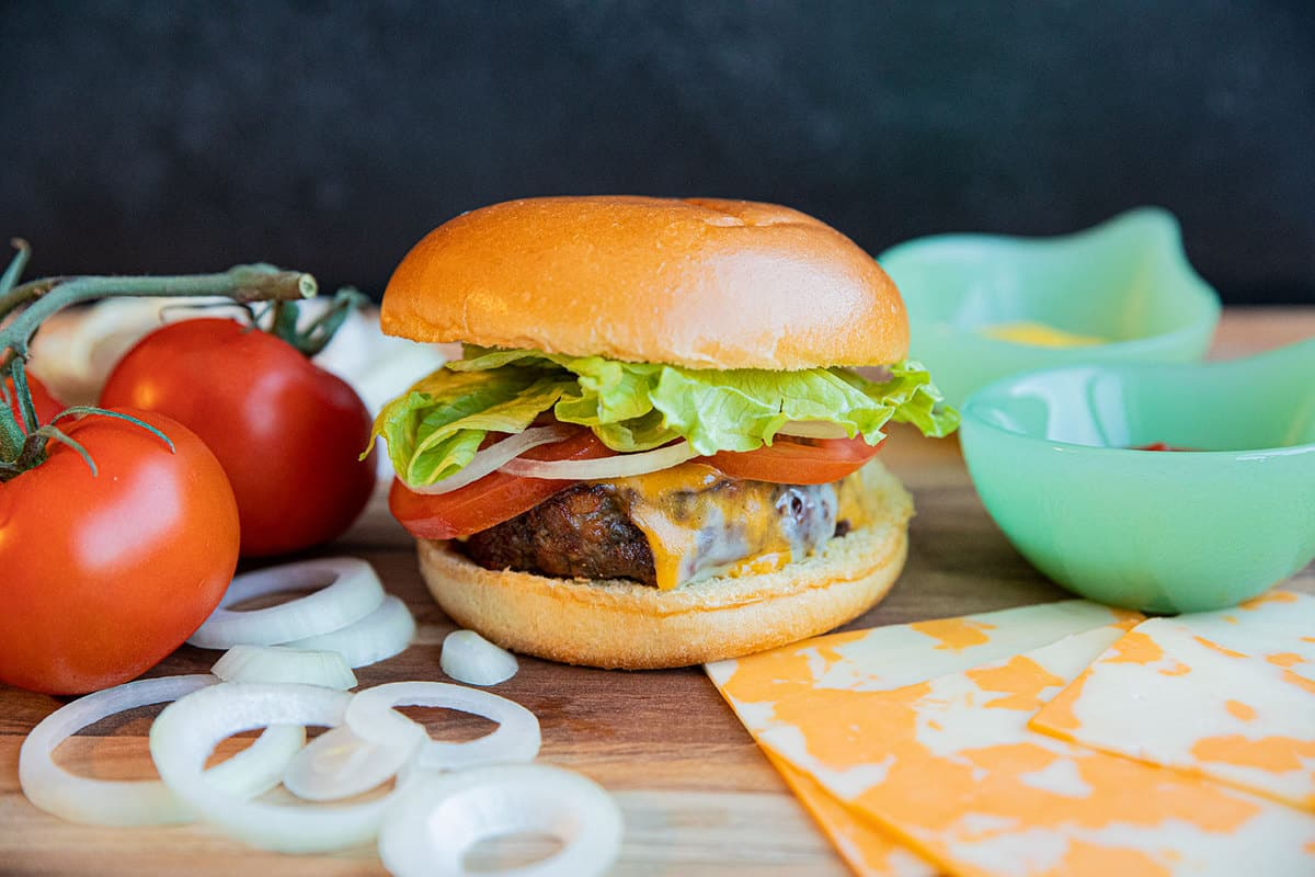 Air Fryer Hamburgers on a wood cutting board with tomatoes, onion, cheese and lettuce.