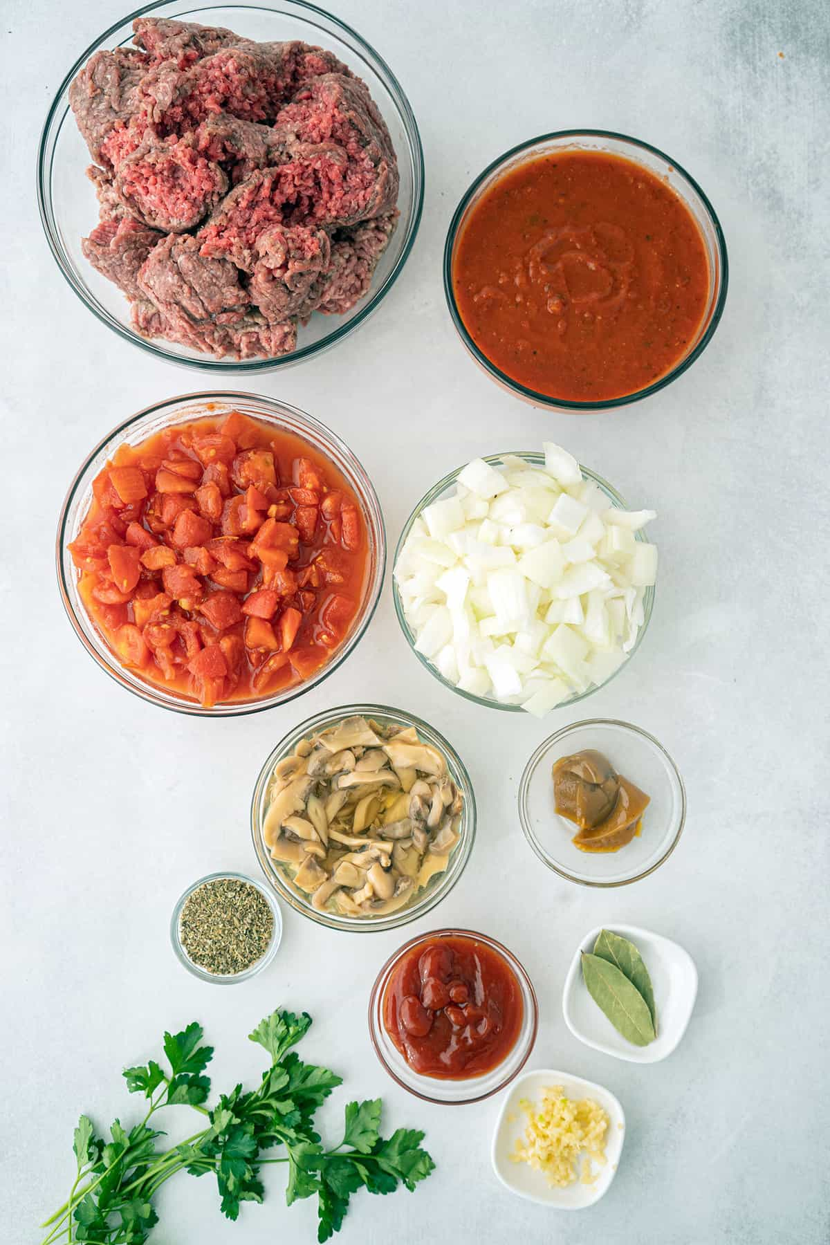 All the ingredients of a meat sauce in separate bowls.