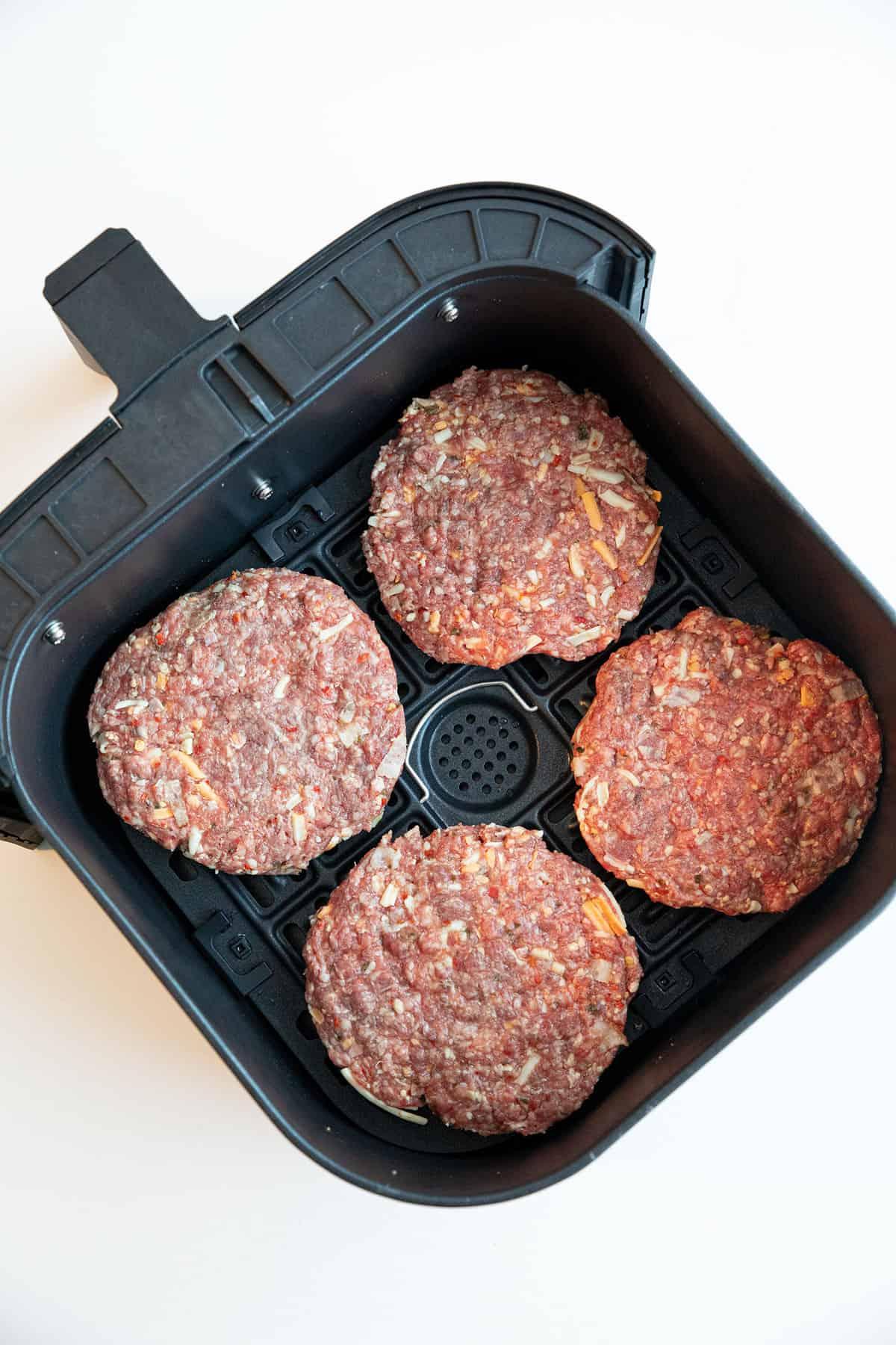Burger patties in an air fryer basket