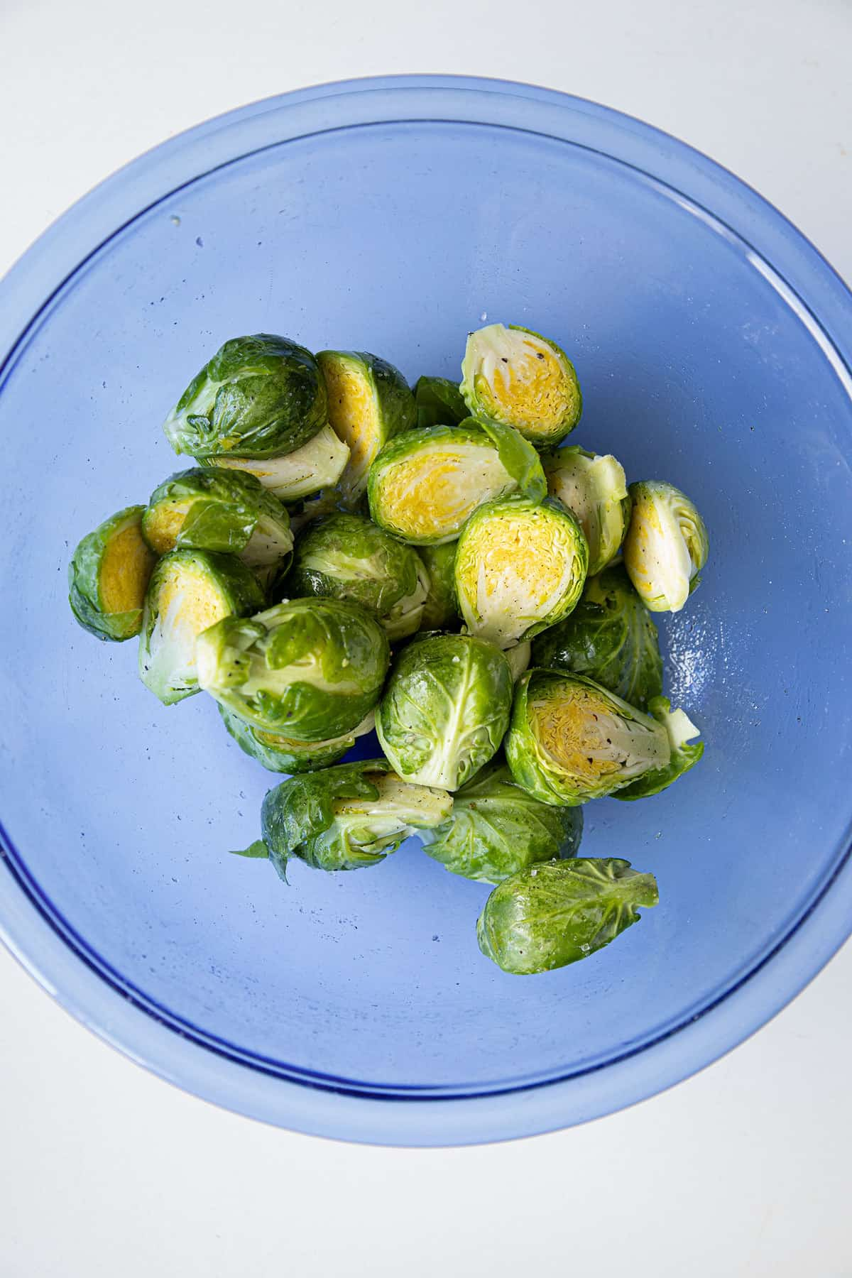 brussel sprouts in a bowl coated in olive oil and salt and pepper