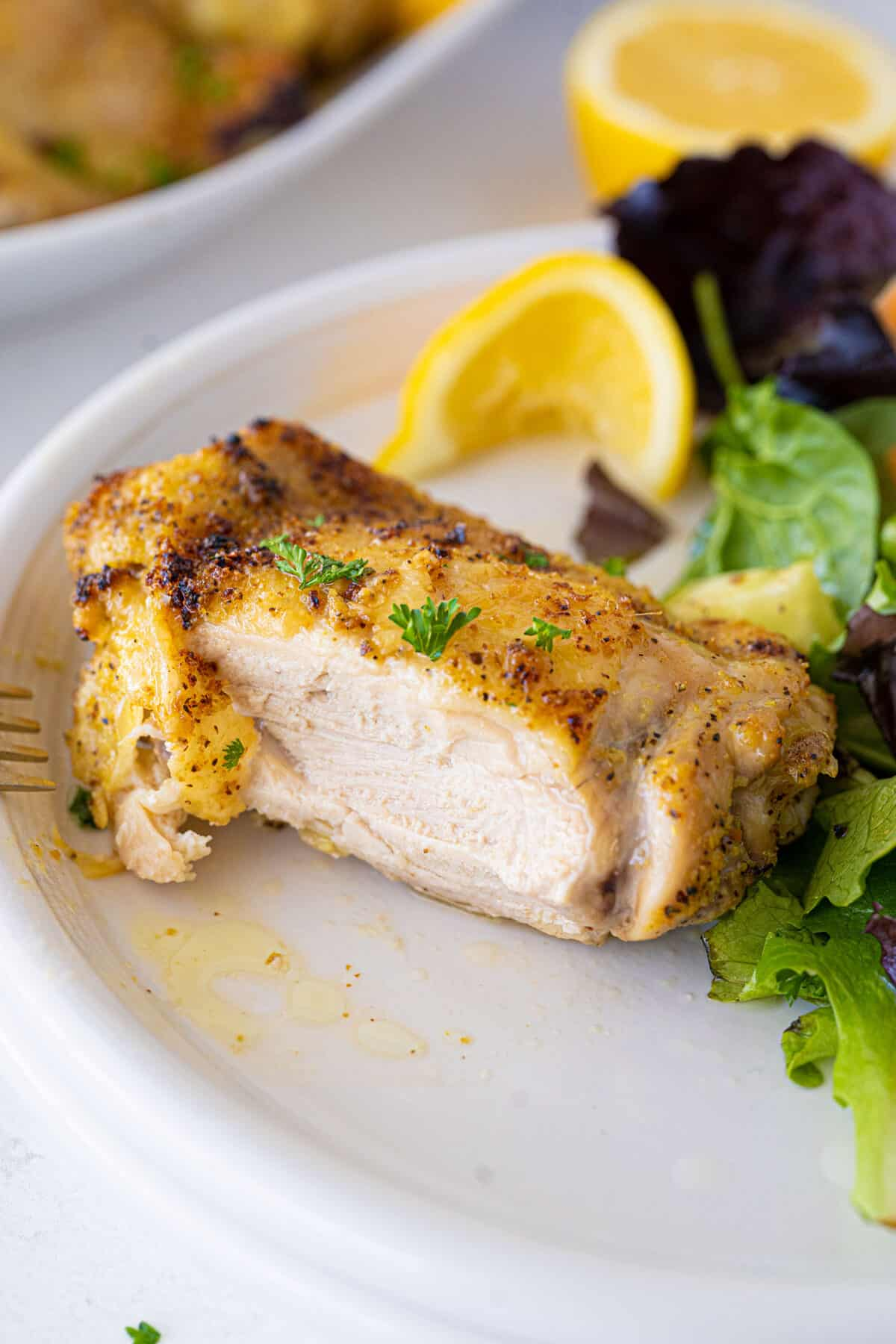 cooked lemon pepper chicken thigh cut in half