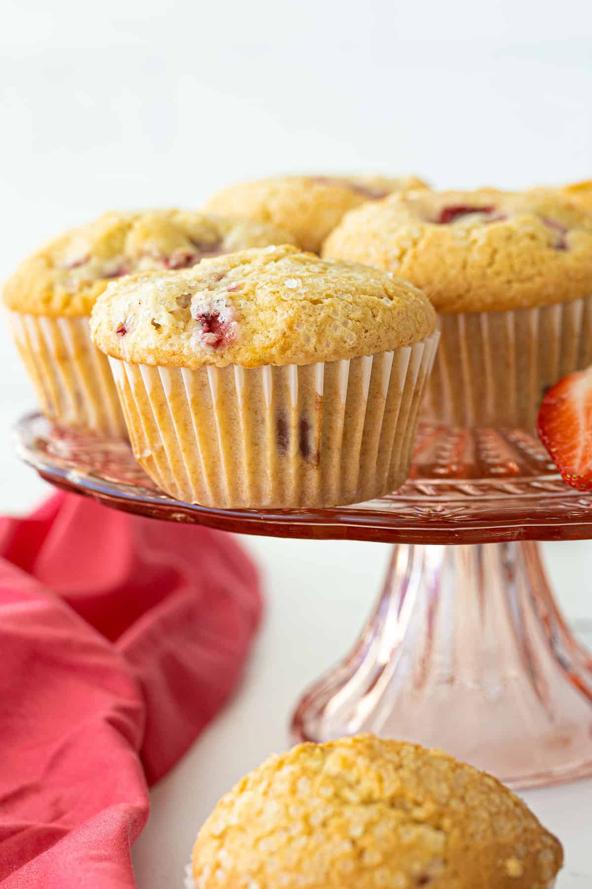 close up of strawberry muffins on a pink platter