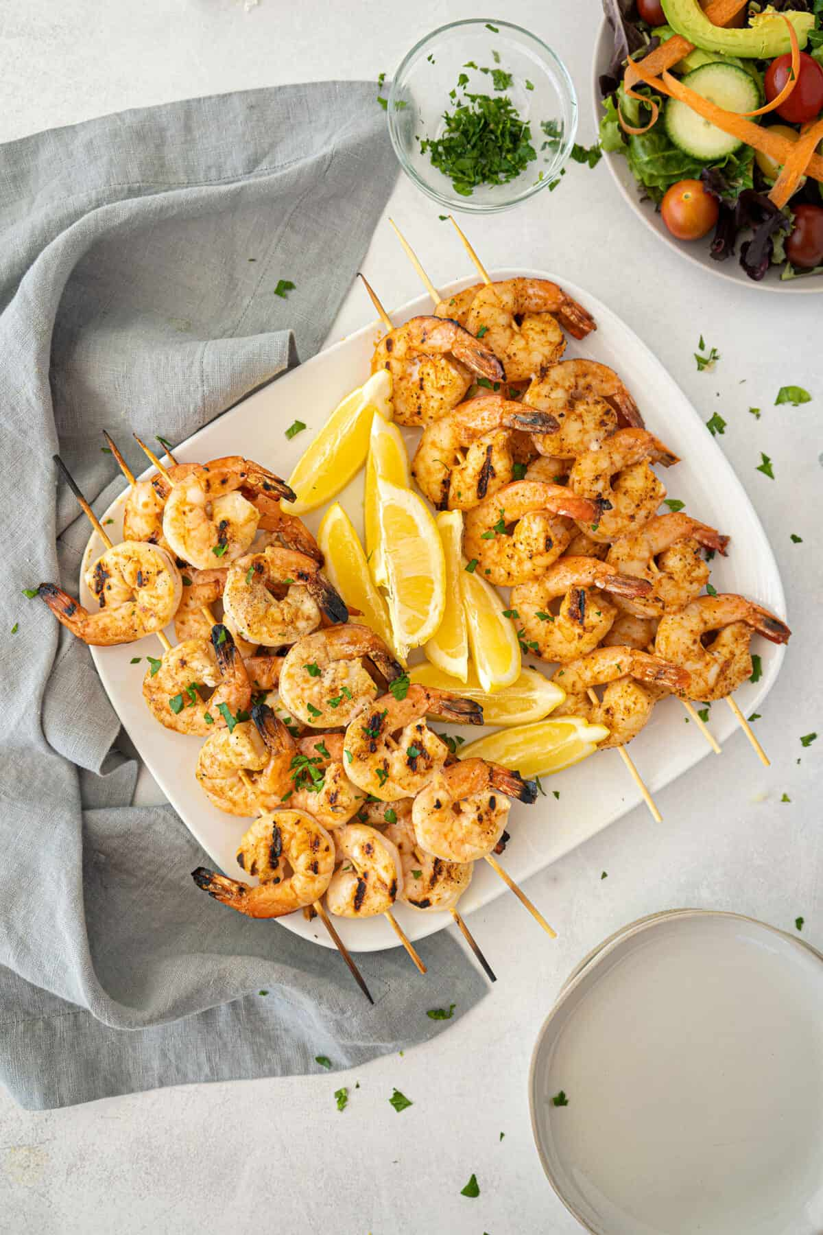 two kinds of grilled shrimp on a white platter