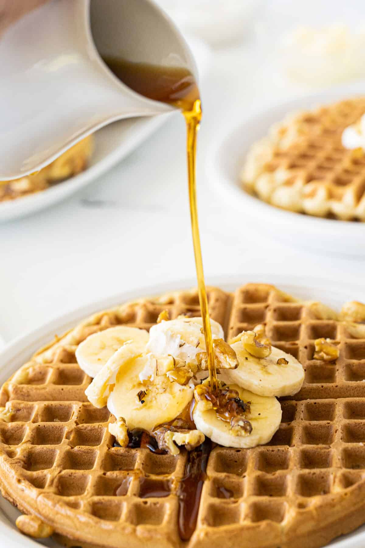 banana waffles with syrup being poured on top