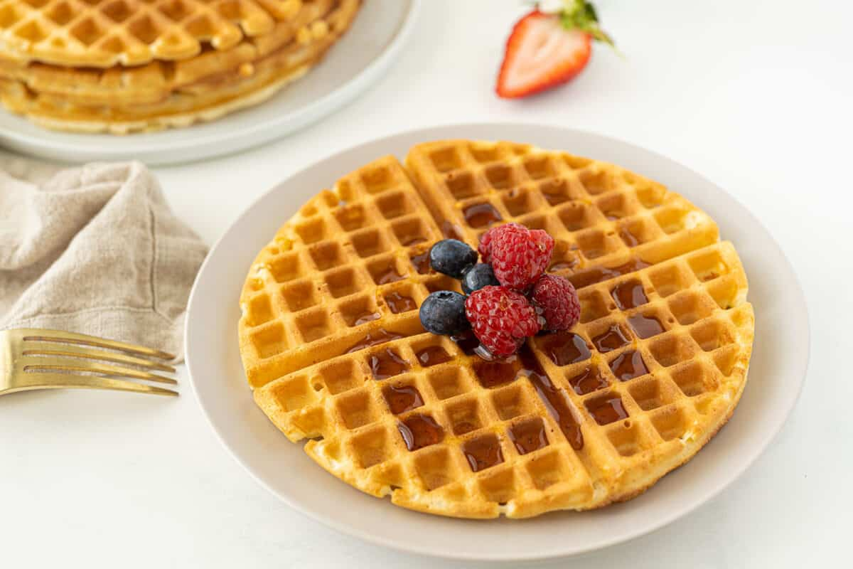 bisquick waffles on a white plate with syrup and berries