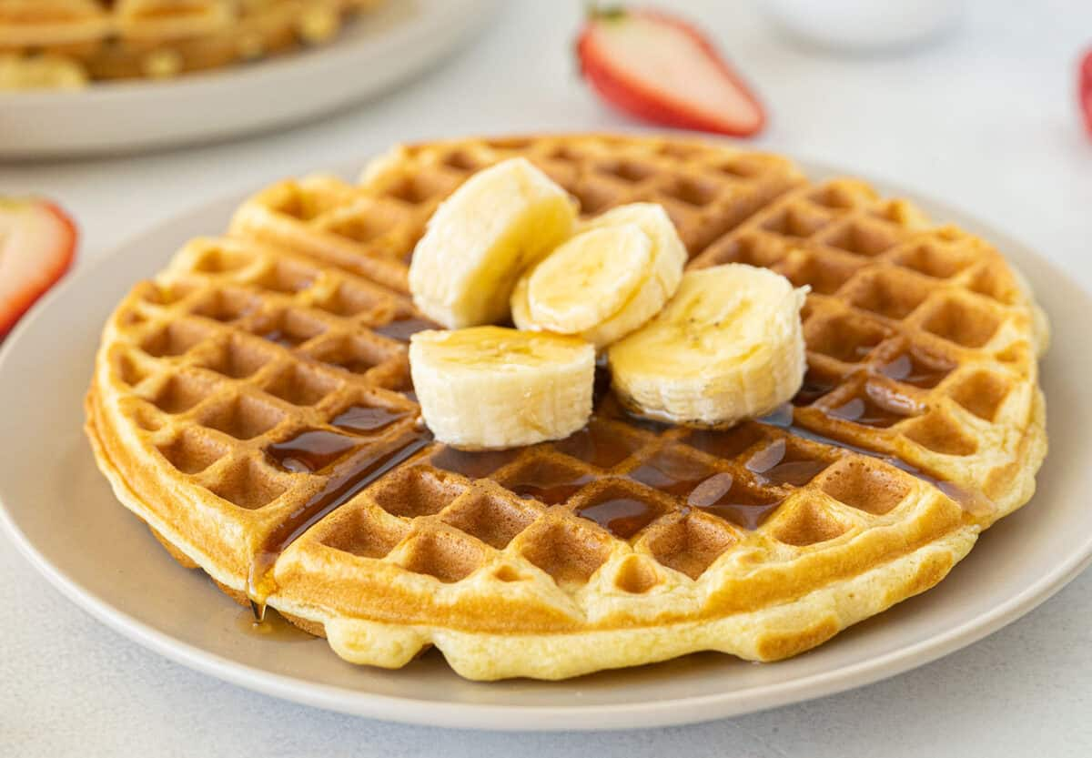 buttermilk waffles with bananas and syrup on top