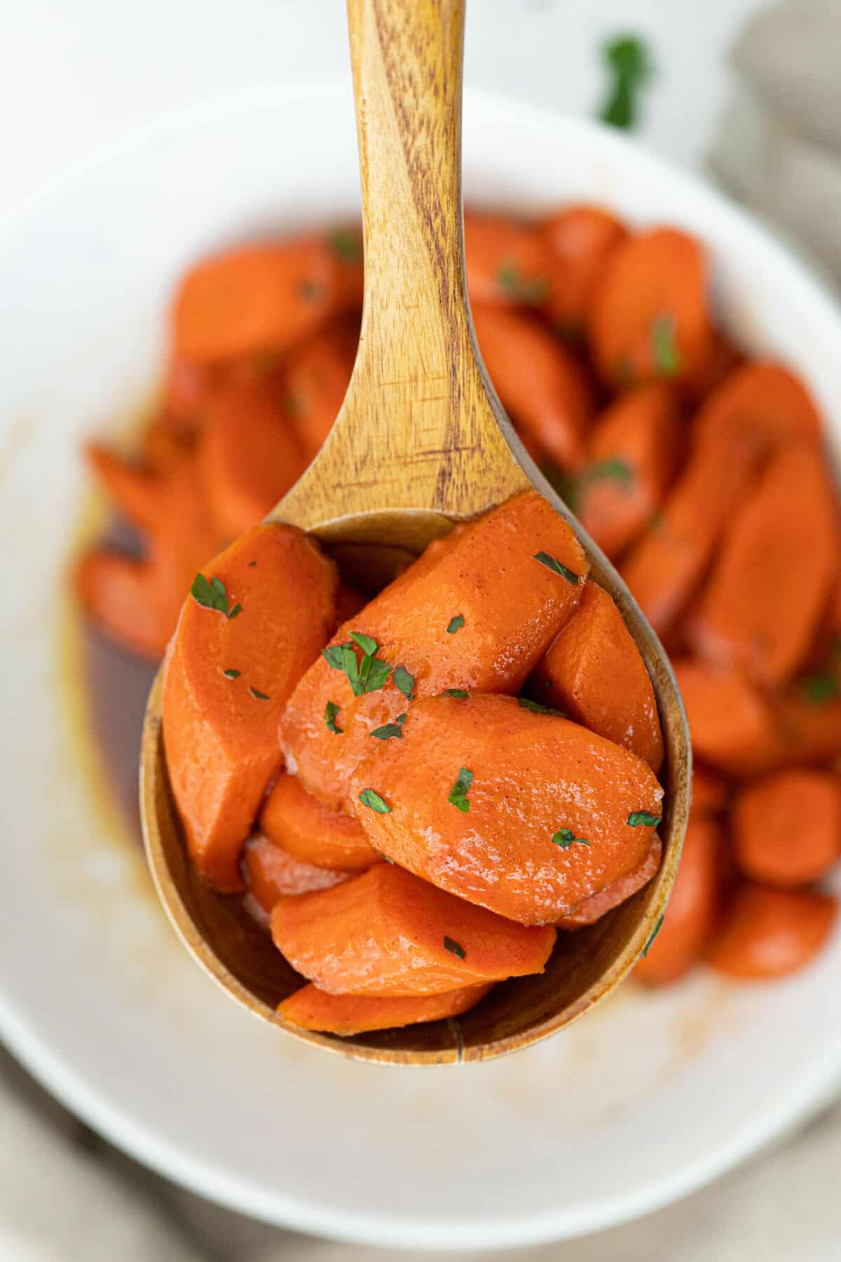 candied carrots on a wooden spoon