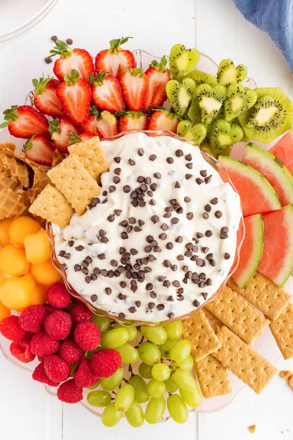 cannoli dip with chocolate chips sprinkled on top surrounded by fruit and cookies