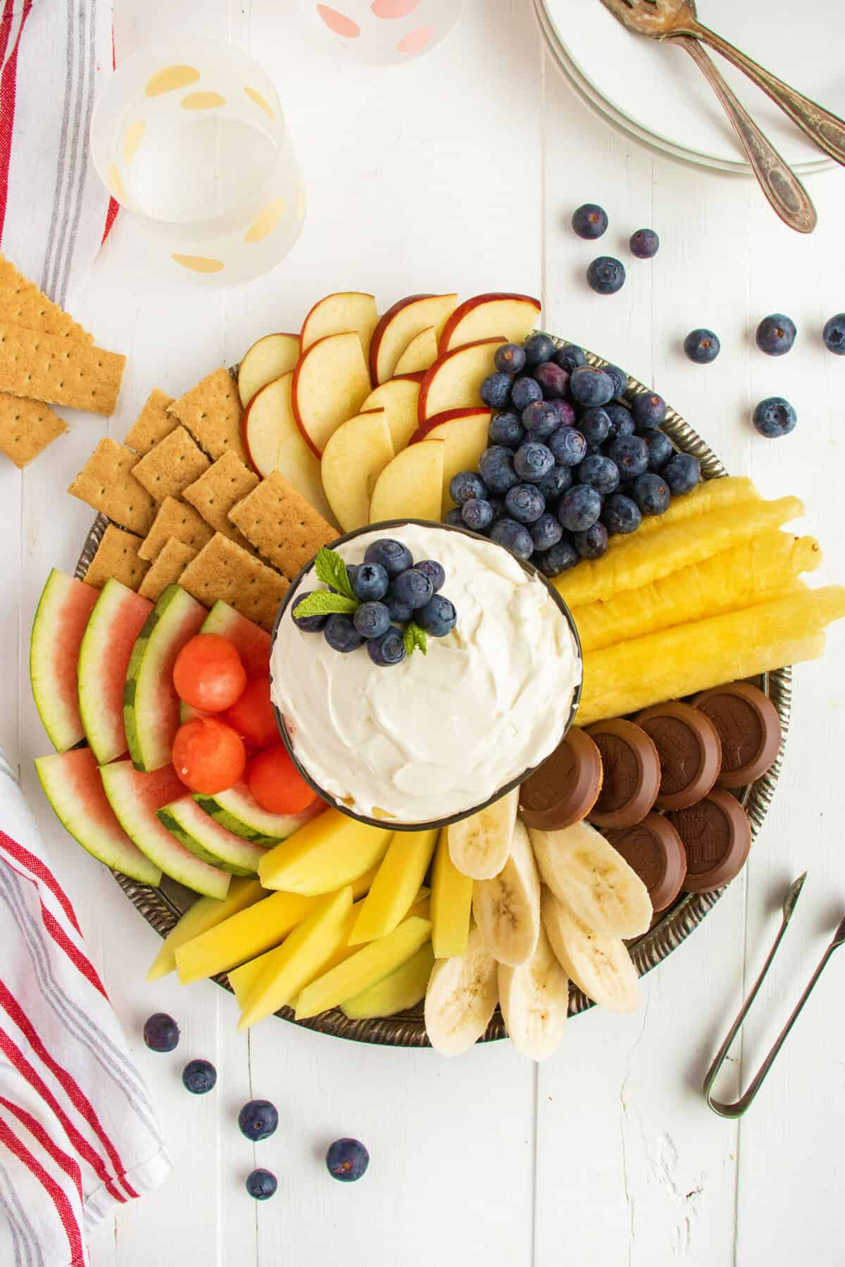cream cheese dip topped with blueberries and surrounded by fruit and cookies