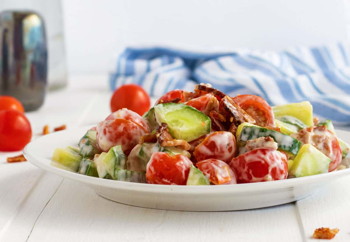 cucumber tomato Salad on a white plate