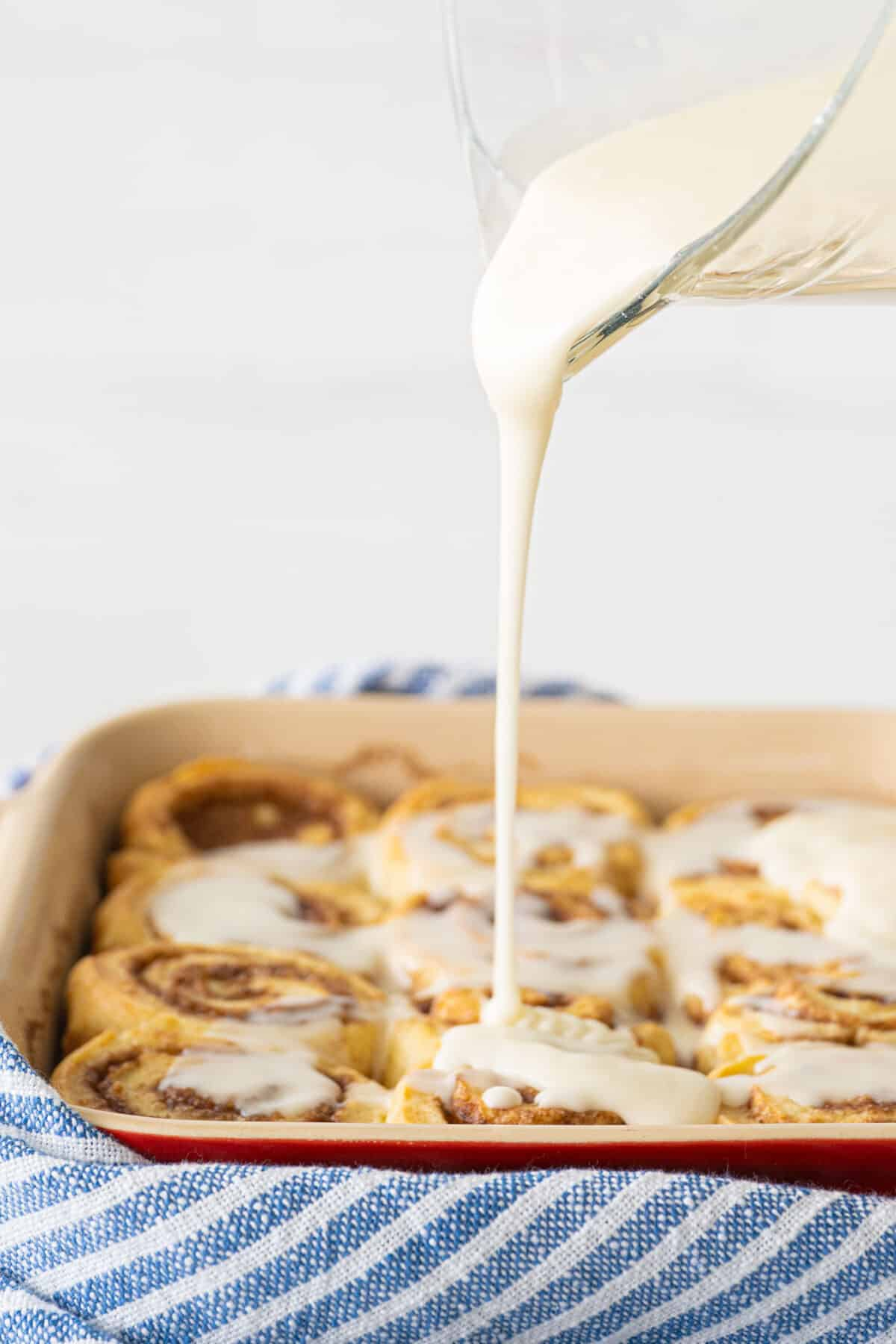 icing being poured over cinnamon rolls in a pan