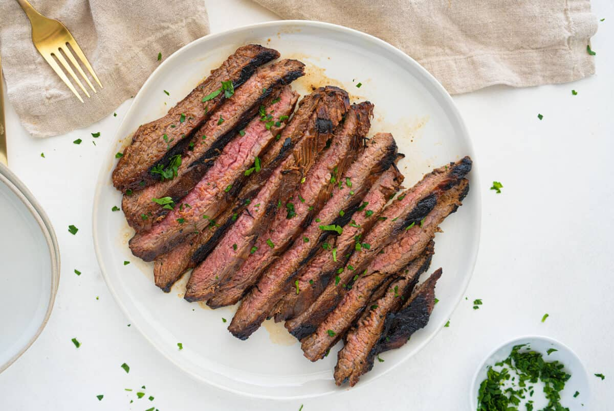 marinated flank steak on a white plate