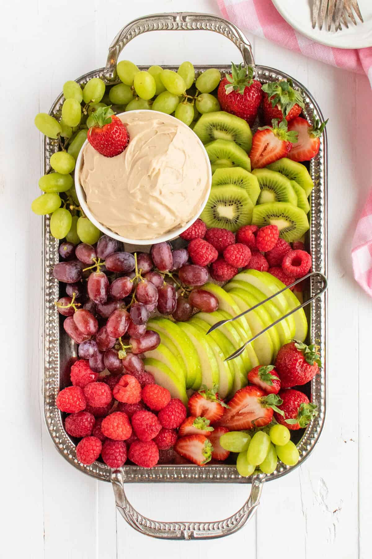 fruit dip on a silver platter surrounded by fruit