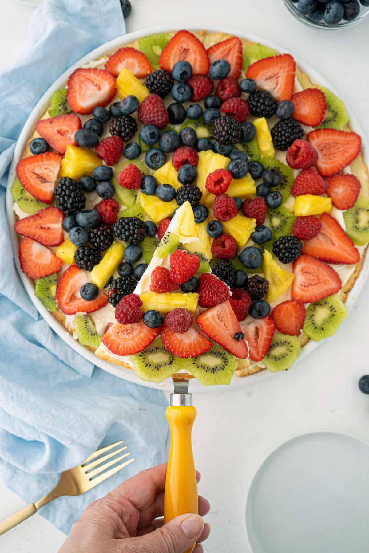lifting a slice of fruit pizza with a cake lifter