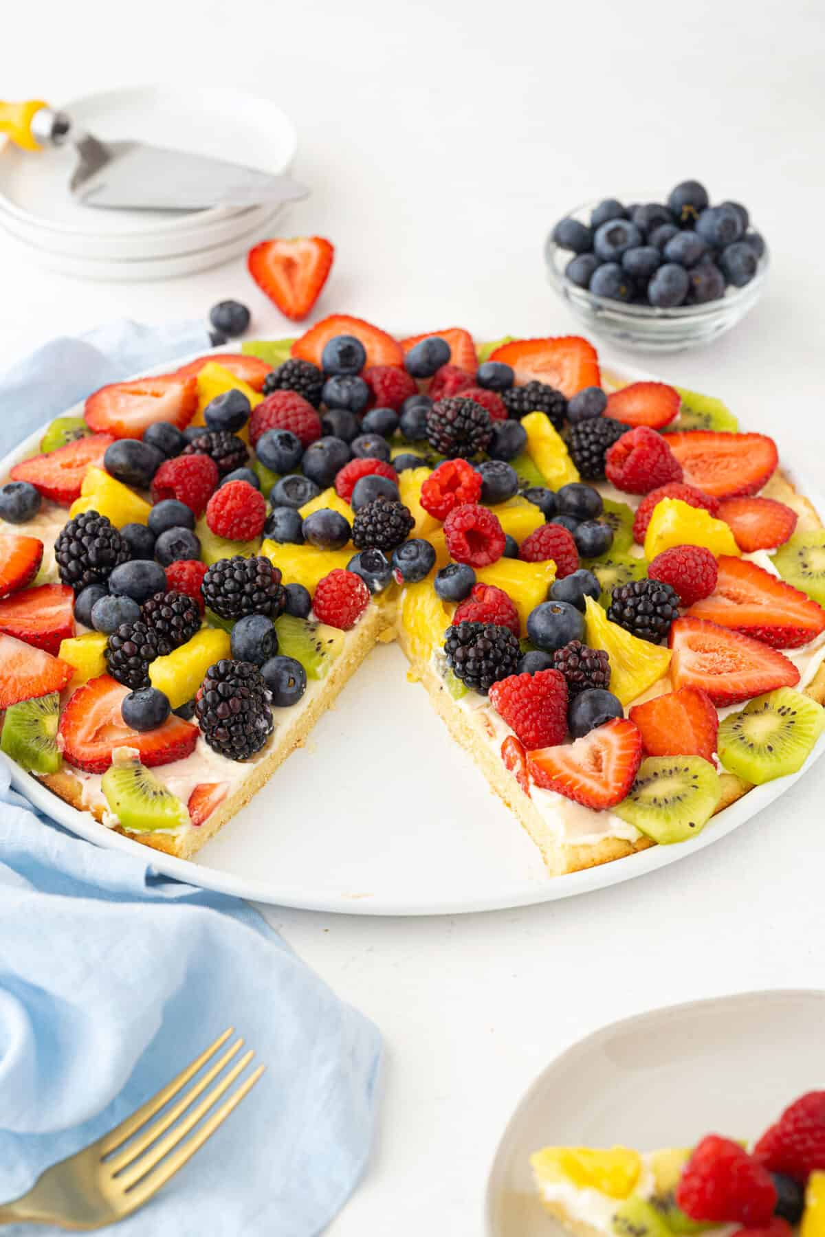 fruit pizza on a white plate with a slice taken out of it